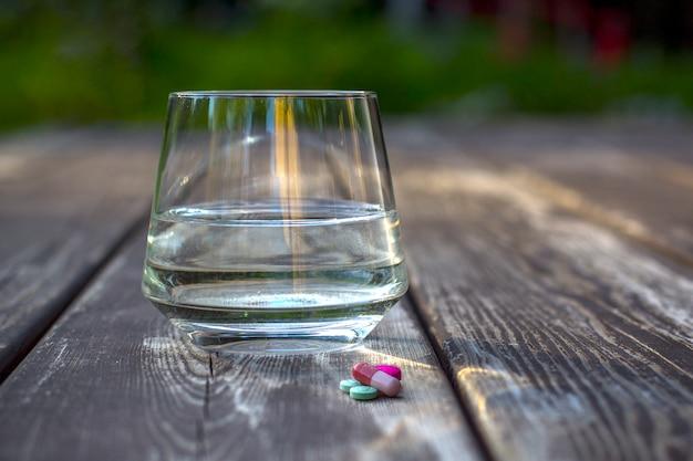 Verre d'eau propre et pilules sur une table en bois