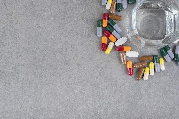 Un verre d'eau pure avec des pilules colorées sur une surface grise