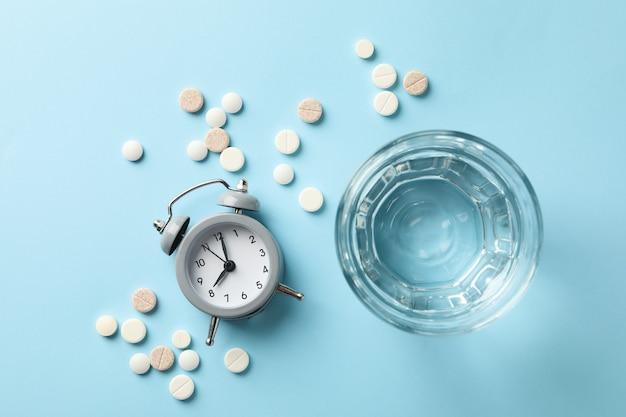 Verre d'eau, réveil et pilules sur bleu
