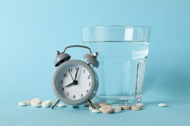 Verre d'eau, réveil et pilules isolés