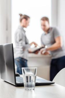 Verre d'eau sur la table de bureau borroso