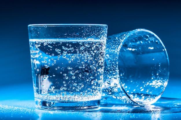 Verre d'eau sur une table dans l'obscurité