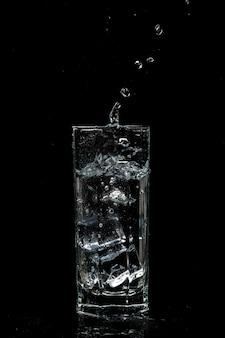 Verre à eau transparent avec des glaçons sur fond de verre isolé noir