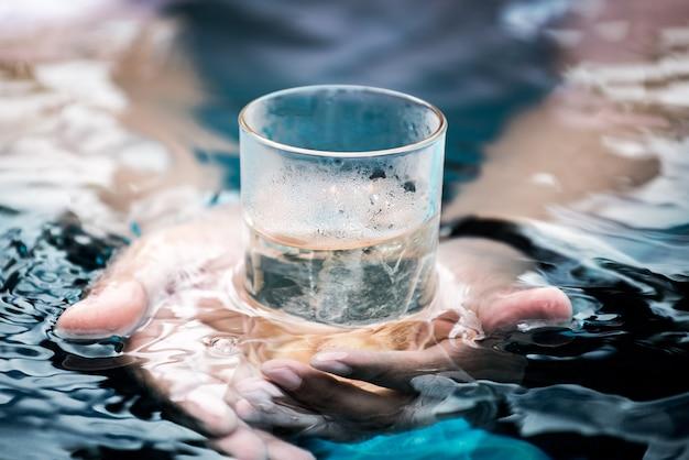 Verre sur l'eau. utilisez une main pour tenir un verre d'eau pour flotter dans l'eau.