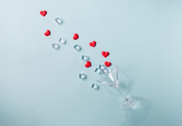 Verre avec éclaboussure de sucre en forme de coeur rouge et de glace. sur fond bleu. concept de saint valentin, anniversaire ou célébration de mariage. mise à plat. vue de dessus. copiez l'espace.