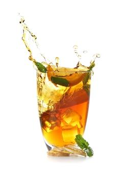 Verre et éclaboussures de délicieux thé au citron avec du gingembre sur une surface blanche