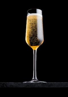 Verre élégant de champagne jaune avec des bulles sur une planche en marbre noir sur fond noir.