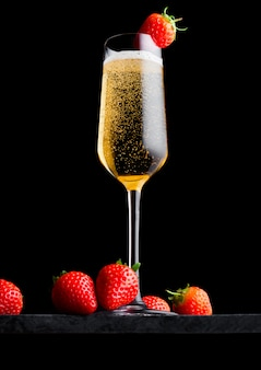 Verre élégant de champagne jaune avec fraise sur le dessus et baies fraîches sur une plaque de marbre noir sur fond noir.