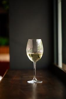 Verre élégant de vin blanc sur comptoir de bar en bois