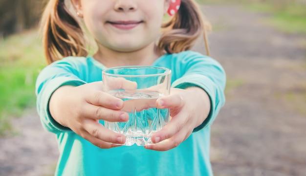 Verre d'enfant d'eau. mise au point sélective. des gamins.