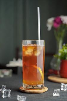 Verre d'expresso avec du jus de citron et des tranches de citron frais sur table en bois
