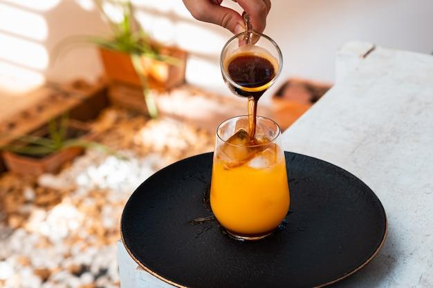Verre d'expresso avec du jus d'orange sur table en bois