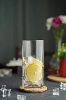 Verre d'expresso avec jus de citron et citron frais tranché sur table en bois et espace copie, cocktail d'été, café infusé à froid ou thé noir. (gros plan, mise au point sélective)
