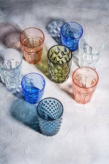 Verre à facettes et géométriques colorés, groupe de verres vides vert, rouge, bleu et transparent pour boisson sur surface de béton en pierre, vue d'angle