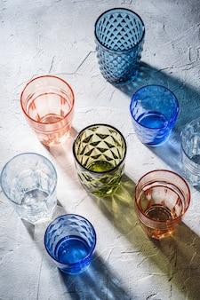 Verre à facettes et géométriques colorés, groupe de verres vides vert, rouge, bleu et transparent pour boisson sur table en béton en pierre, vue d'angle