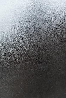 Verre de fenêtre avec des gouttes d'eau. surface grise abstraite avec des gouttes et des taches. cadre vertical.