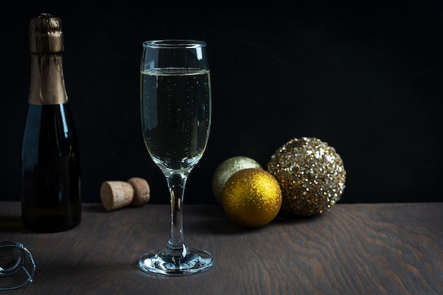 Verre flûte de champagne mousseux sec avec des boules de noël dorées et bouteille sur table en bois foncé