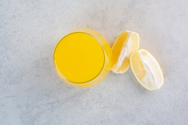 Verre frais de limonade avec des tranches de citron sur gris.