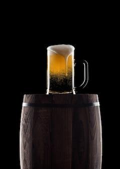 Verre froid de bière artisanale sur vieux tonneau en bois sur fond noir avec rosée et bulles