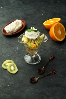 Un verre de fruits mélangés avec de la crème
