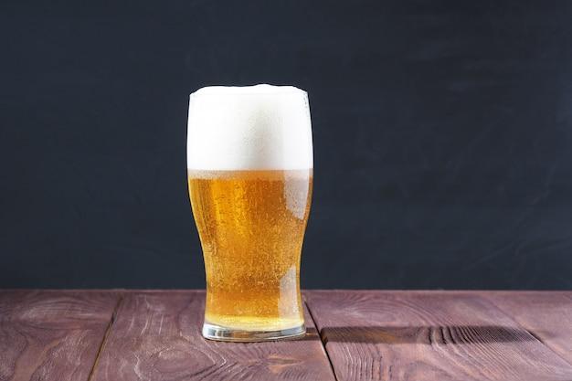 Un verre givré de bière légère avec un bouchon mousseux sur une table en bois