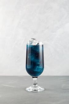 Verre de gros plan de cocktail lagon bleu. grand verre de boisson rafraîchissante sur fond gris clair.