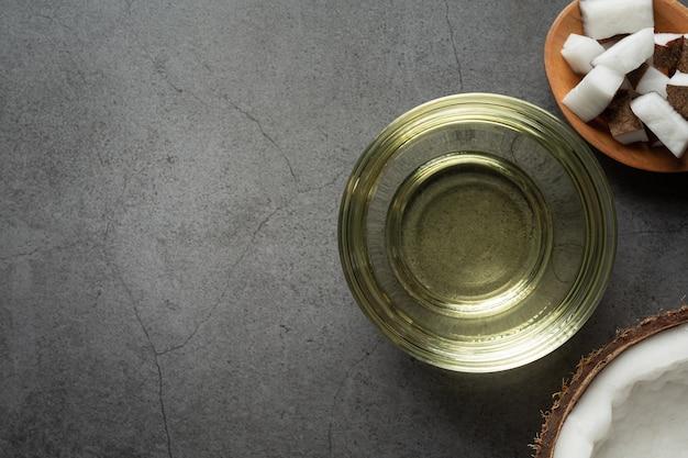 Verre d'huile de coco mis sur un sol sombre