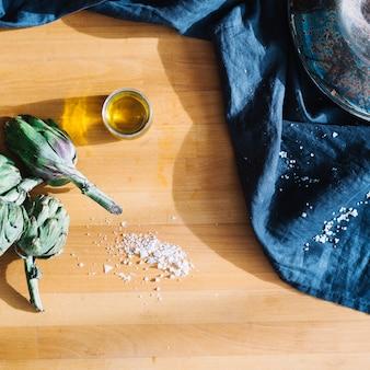 Verre d'huile près d'artichauts et de sel