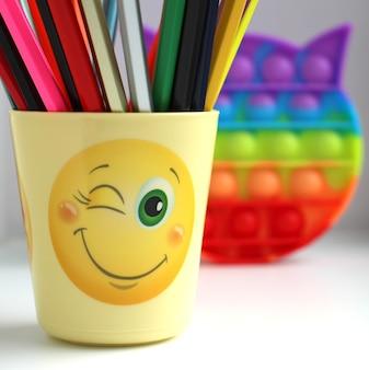 Un verre jaune avec des crayons de couleur et un popit jouet antistress coloré