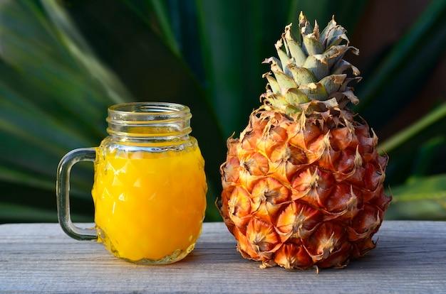 Verre de jus d'ananas frais et de fruits d'ananas mûrs sur une table en bois rustique.jus d'ananas fraîchement pressé avec de la paille à boire.aliments sains, régime alimentaire ou concept de nourriture végétalienne.