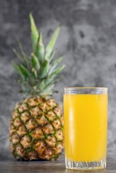 Verre de jus d'ananas avec des fruits frais sur fond gris