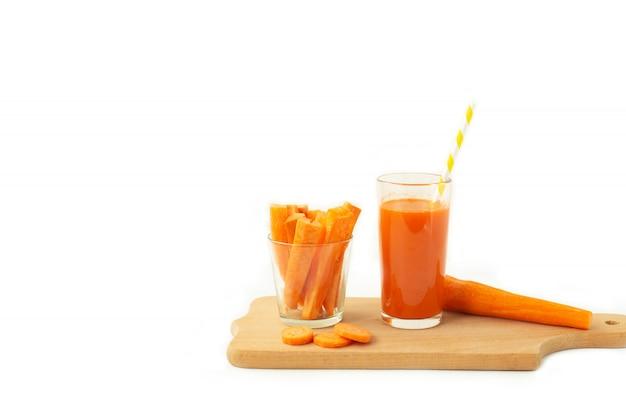 Verre de jus de carotte et de carotte fraîche sur une planche à découper
