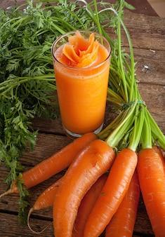 Verre de jus de carottes fraîches avec carottes biologiques fraîches