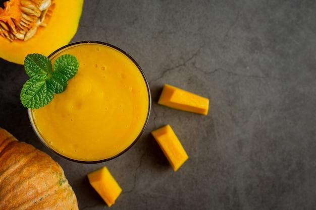 Un verre de jus de citrouille et de citrouilles crues hachées sur un sol sombre