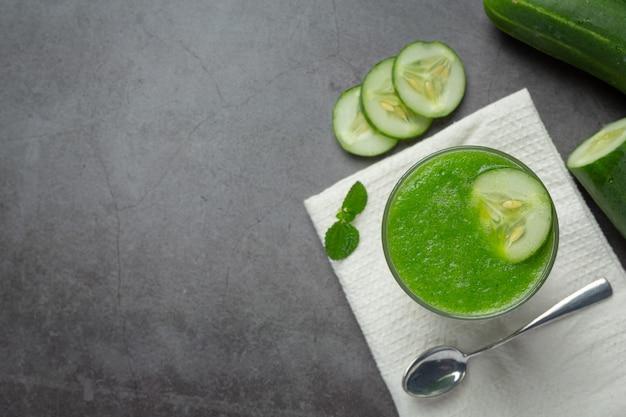 Verre de jus de concombre frais sur fond sombre