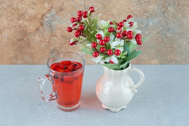Verre de jus d'églantier et de fleurs artificielles sur table bleue. photo de haute qualité