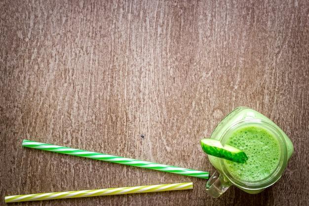 Verre de jus d'épinards sur fond en bois. mise à plat avec place pour le texte. concept d'alimentation végétalienne et saine