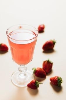 Verre de jus de fraise sur fond uni