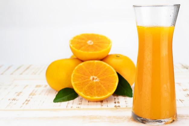 Verre de jus de fruit d'orange frais sur blanc
