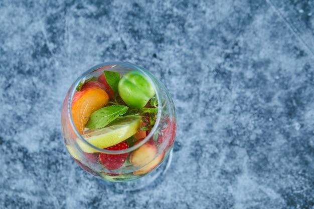 Un verre de jus avec des fruits entiers à l'intérieur sur une surface bleue