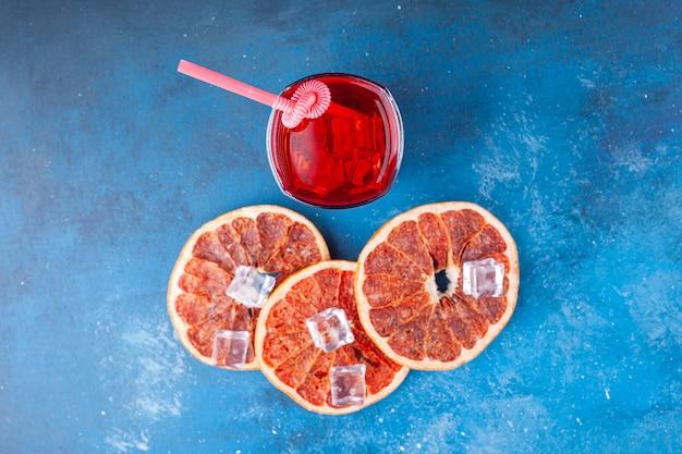 Verre de jus de fruits frais avec du pamplemousse en tranches sur fond bleu.