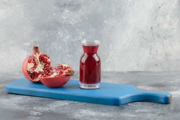 Verre de jus de fruits frais avec des fruits de grenade mûrs à bord bleu.