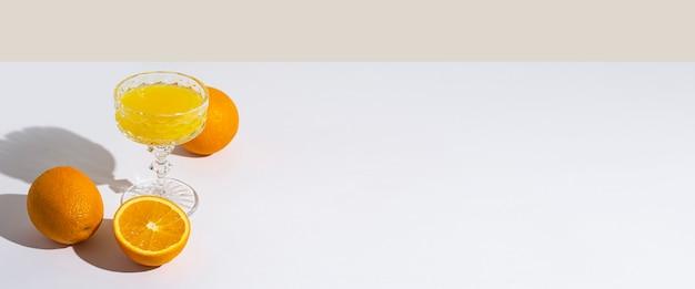 Verre avec jus de fruits frais et oranges sur fond clair