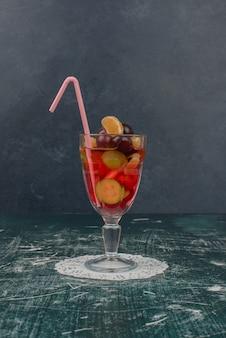 Verre de jus de fruits mélangés sur table en marbre.