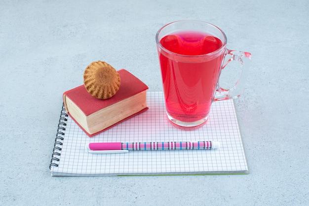 Verre de jus, gâteau, cahier et stylo surface bleue.