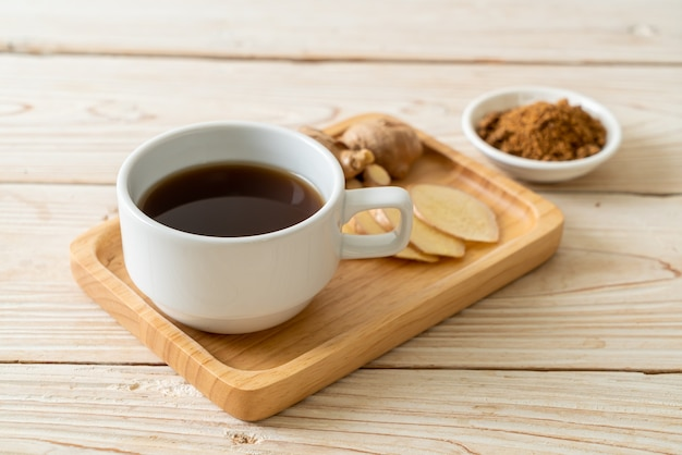 Verre de jus de gingembre chaud et sucré avec des racines de gingembre - style de boisson saine