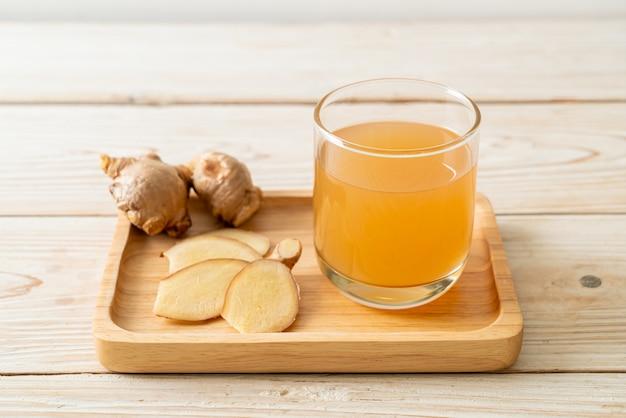 Verre de jus de gingembre frais et chaud avec des racines de gingembre. style de boisson saine