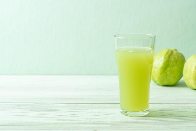 Verre de jus de goyave frais avec des fruits de goyave frais sur table en bois