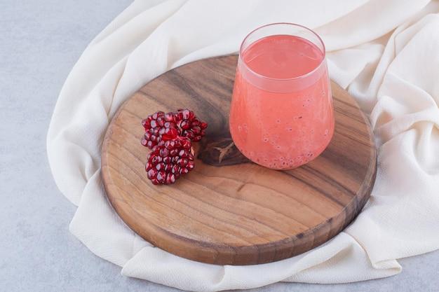 Un verre de jus de grenade sur planche de bois avec des graines. photo de haute qualité
