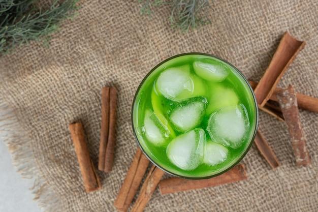 Un verre de jus de kiwi et des bâtons de cannelle sur de la toile de jute